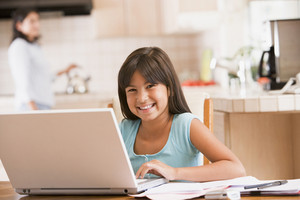 Young girl in kitchen with laptop and paperwork smiling with woman in background