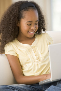 Young girl in living room using laptop and smiling