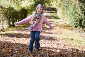 Young girl running through autumn woods