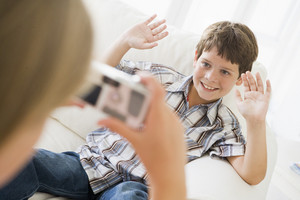 Young girl taking picture of smiling young boy with camera phone indoors