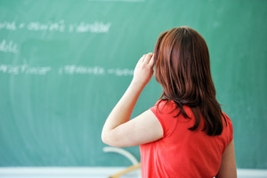 Young girl thinking in front of a blackboard