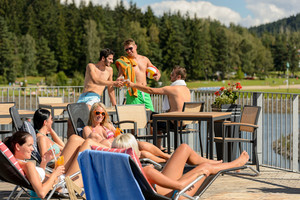 Young group of friends enjoying summertime drinking and sunbathing
