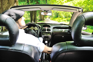 Young guy driving a sports car in forest