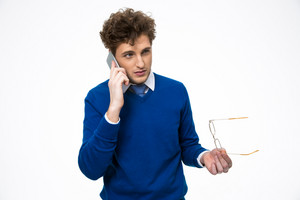 Young handsome business man talking on the phone and holding glasses