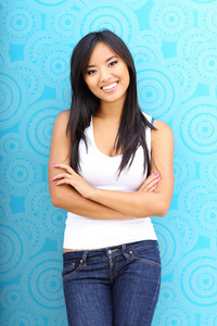 Young happy asian woman standing against blue background