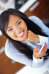 Young happy asian woman using her smartphone