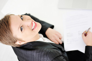 Young happy business woman at office making successful deal and signing a contract