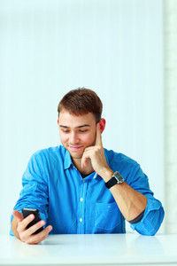 Young happy businessman sitting at the table and holding smartphone in office