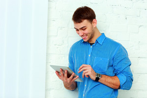 Young happy businessman standing with tablet computer near the wall at office