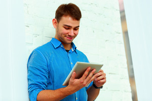 Young happy businessman standing with tablet computer near the wall
