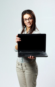 Young happy businesswoman showing laptop on gray background