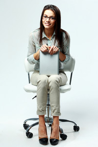 Young happy businesswoman sitting on office chair and holding tablet computer on gray background
