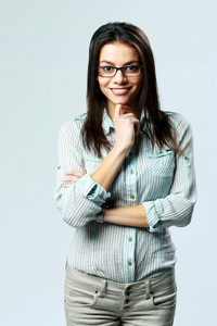 Young happy businesswoman wearing glasses standing on gray background