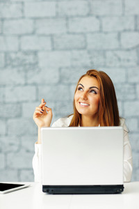 Young happy businesswoman with laptop pointing up at copyspace