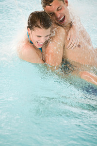Young happy couple have fun under water stream in swimming pool