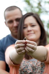 Young happy couple holding a diamond engagement ring.  Shallow depth of field with focus on the ring.