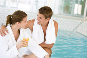 Young happy couple relax at swimming pool,drink juice