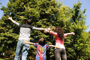 Young happy family in nature with opened arms looking up and breathing fresh air