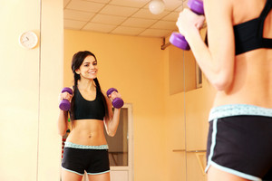 Young happy fit woman doing exercises with dumbells and looking at her reflection at gym