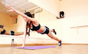 Young happy fit woman doing fitness exercises at gym