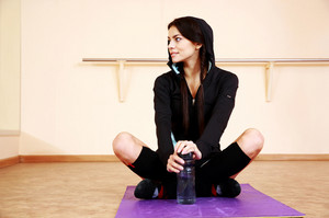 Young happy fit woman sitting on yoga mat and looking away at gym
