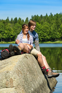 Young happy hikers couple lounging at lake beautiful nature