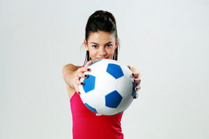 Young happy sport woman giving you a soccer ball on gray background
