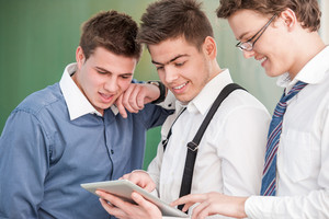 Young happy student showing a tablet to his friends in front of a blackboard