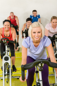 Young happy woman at spinning class enjoy gym workout