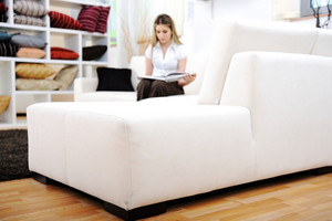 Young happy woman read book on sofa in living room (focus on couch)