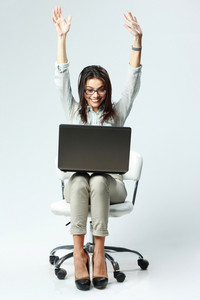 Young happy woman with arms up sitting on the chair with laptop on gray background