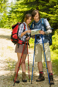 Young hiker couple standing and checking the map in nature