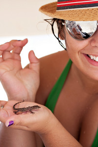 Young Hispanic woman happily holds a wild tropical lizard found on the island of Culebra Puerto Rico. Shallow depth of field.