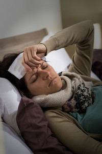 Young ill woman in bed having high fever flu