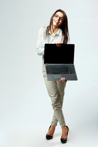 Young laughing businesswoman showing laptop on gray background