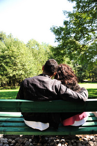 young loving couple on the bench in park