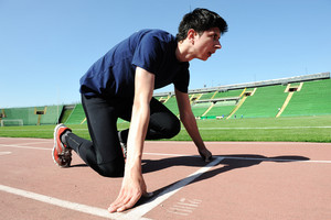 young male  athlete is at the start of the treadmill at the stadium