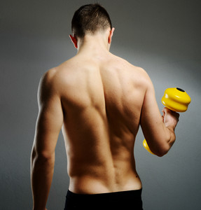 Young male bodybuilder doing heavy weight exercise with dumbbells against dark background