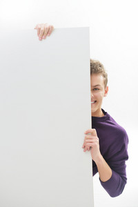 Young male isolated on white holding a cardboard