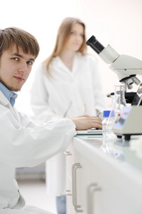 Young male researcher with a microscope and writing notes on laptop at laboratory