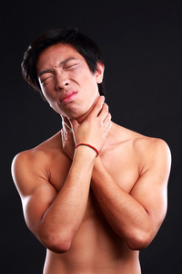 Young male suffering from neck pain on black background