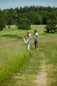 Young man and woman exercising in spring meadow on sunny day