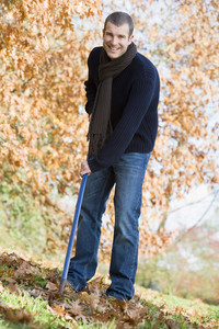 Young man clearing autumn leaves in garden