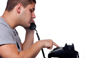 Young man dials a vintage rotary phone isolated over a white background.