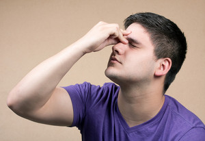 Young man has an intense headache. He might be experiencing stress during a time of economic crisis or other hardship.