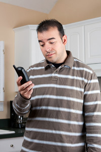 Young man holding a cordless phone handset in his hand with an annoyed or skeptical expression on his face.