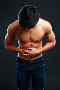 Young man holding his sick stomach in pain on black background