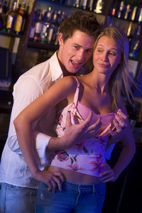 Young man in a nightclub grabbing young women's breasts from behind