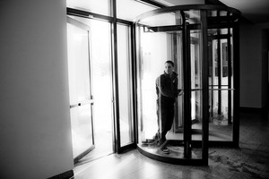 Young man in his twenties walks through a revolving doorway entrance. Black and white.