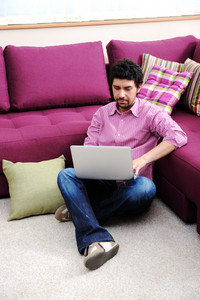 Young man on sofa with laptop